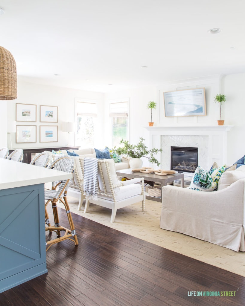 A bright, light-filled living room with linen sofas, white spindle chairs and blue and white accents.