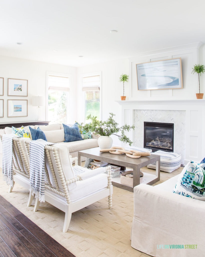 White couches with blue pillows and a striped blanket hanging on the back of the chair.    There is a fireplace in the living room as well.