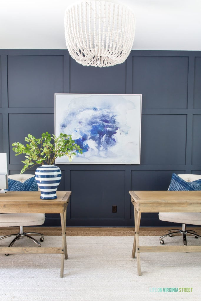 A home office with a navy blue board and batten accent wall, white and jute rug, wood desks, linen office chairs, white wood bead chandelier, blue and white abstract art, and a blue and white striped vase.