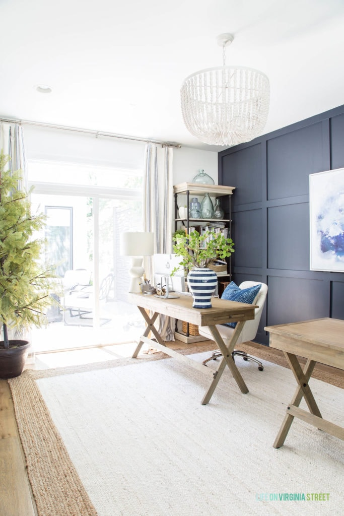 A home office with navy blue and white walls, a jute rug, white oak hardwood floors, light wood desks, linen office chairs, and a white wood bead chandelier.