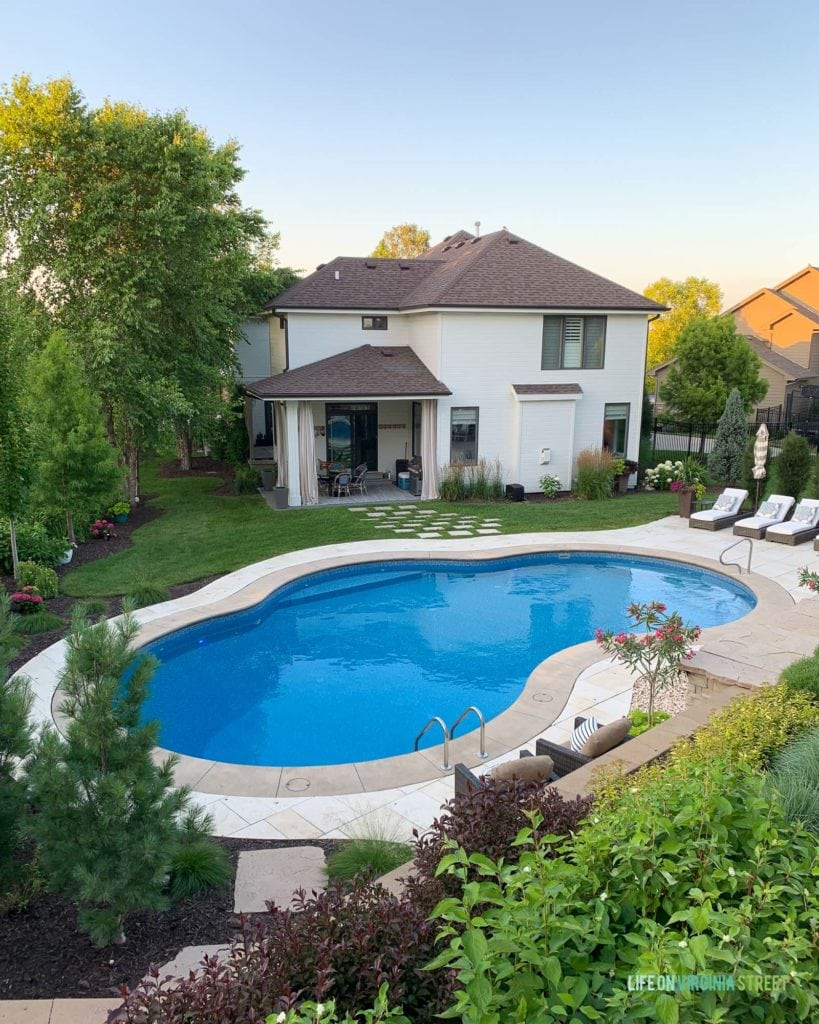 A white house with brown roof from the backyard view with an oasis shaped swimming pool.