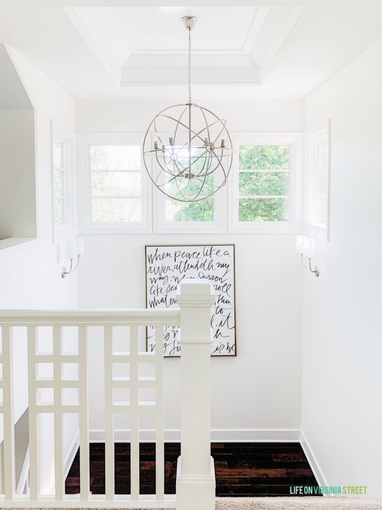 The landing on the stairwell with a chandelier an a painting quote hanging on the wall.