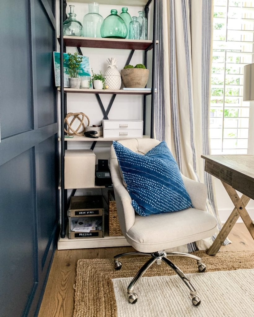 A home office space with navy blue wall, wood and metal bookcase, linen desk chair, jute rug, blue pillow and reclaimed wood desk.