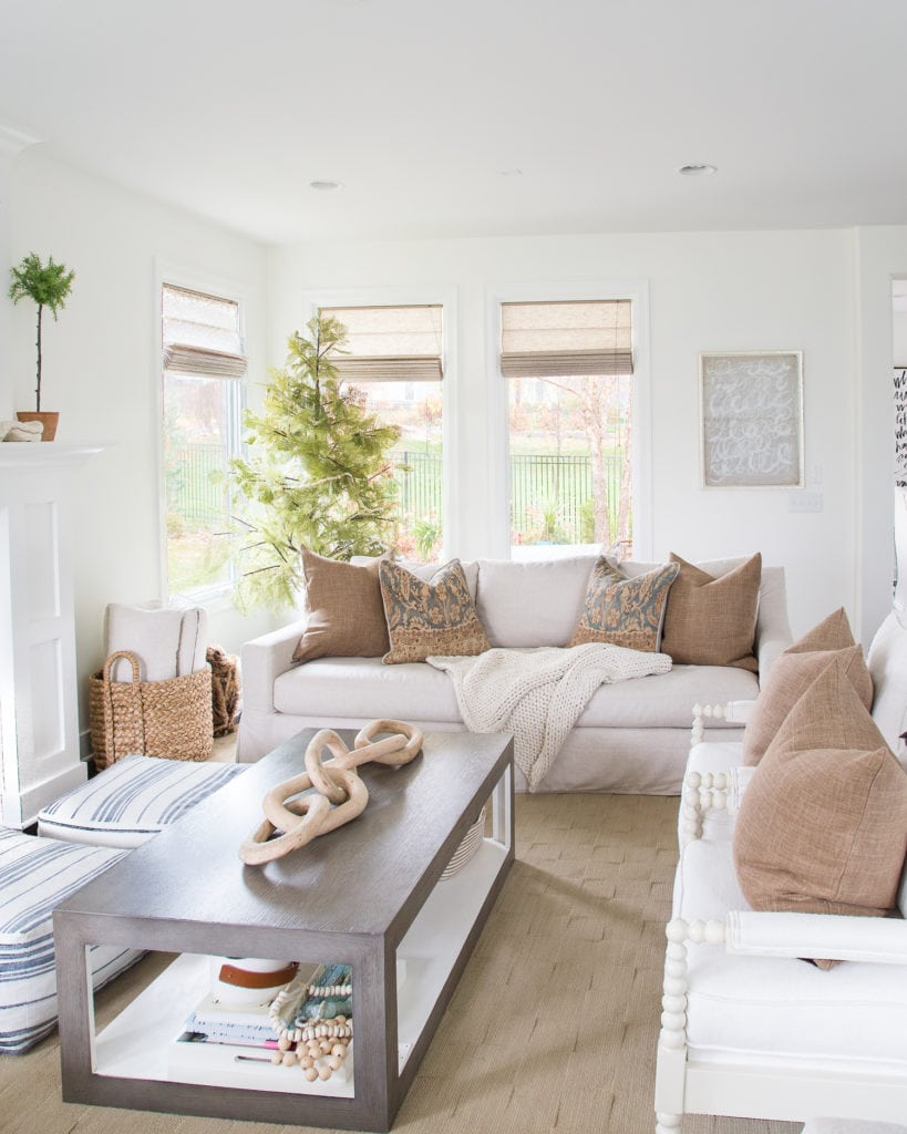 A fall living room decorated in brown tones with blue and white accents. Walls are Benjamin Moore Simply White.