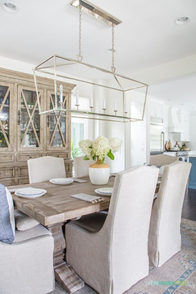 A neutral dining room with linen chairs, reclaimed wood table, wood hutch, silver Darlana linear chandelier, and blue and white accents. I love the limelight hydrangeas as the centerpiece on this tablescape!