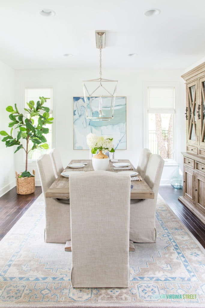 A dining room with Benjamin Moore Simply White walls, linen dining chairs, reclaimed wood dining table, and blue and white accents decorated for summer!