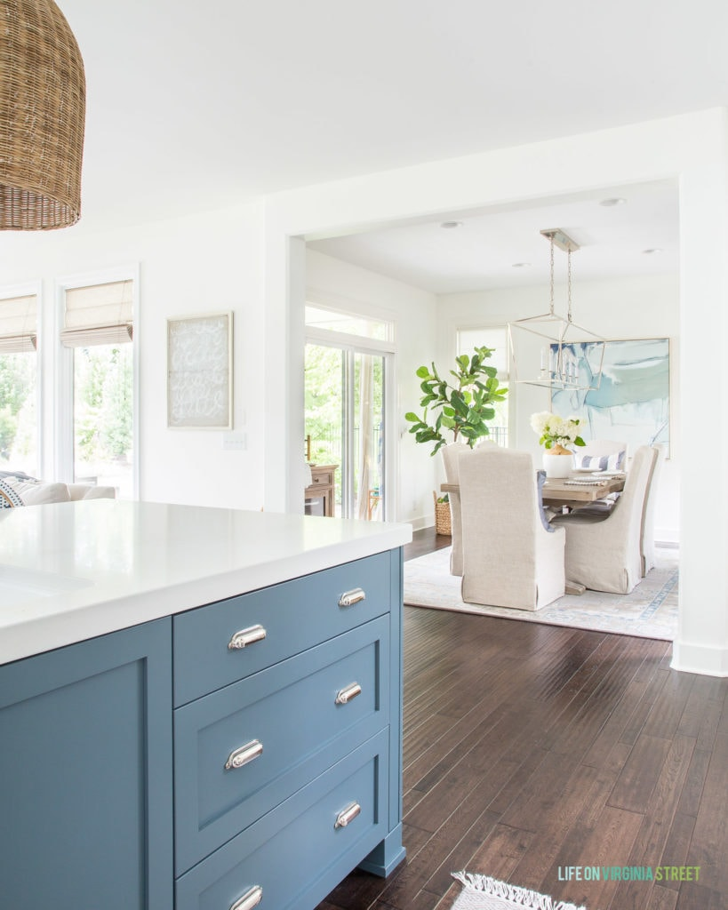 A blue kitchen island (Benjamin Moore Providence Blue) looking into a summer dining room painted Benjamin Moore Simply White. I love the light and airy coastal vibes in this home!
