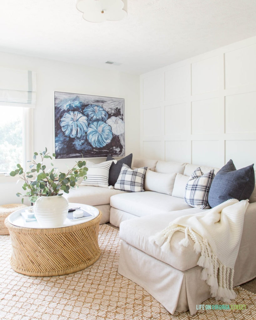 A fall living room with white board and batten grid wall, blue pumpkin abstract art, linen sectional sofa, jute rug, bamboo coffee table, and blue and white plaid pillows.