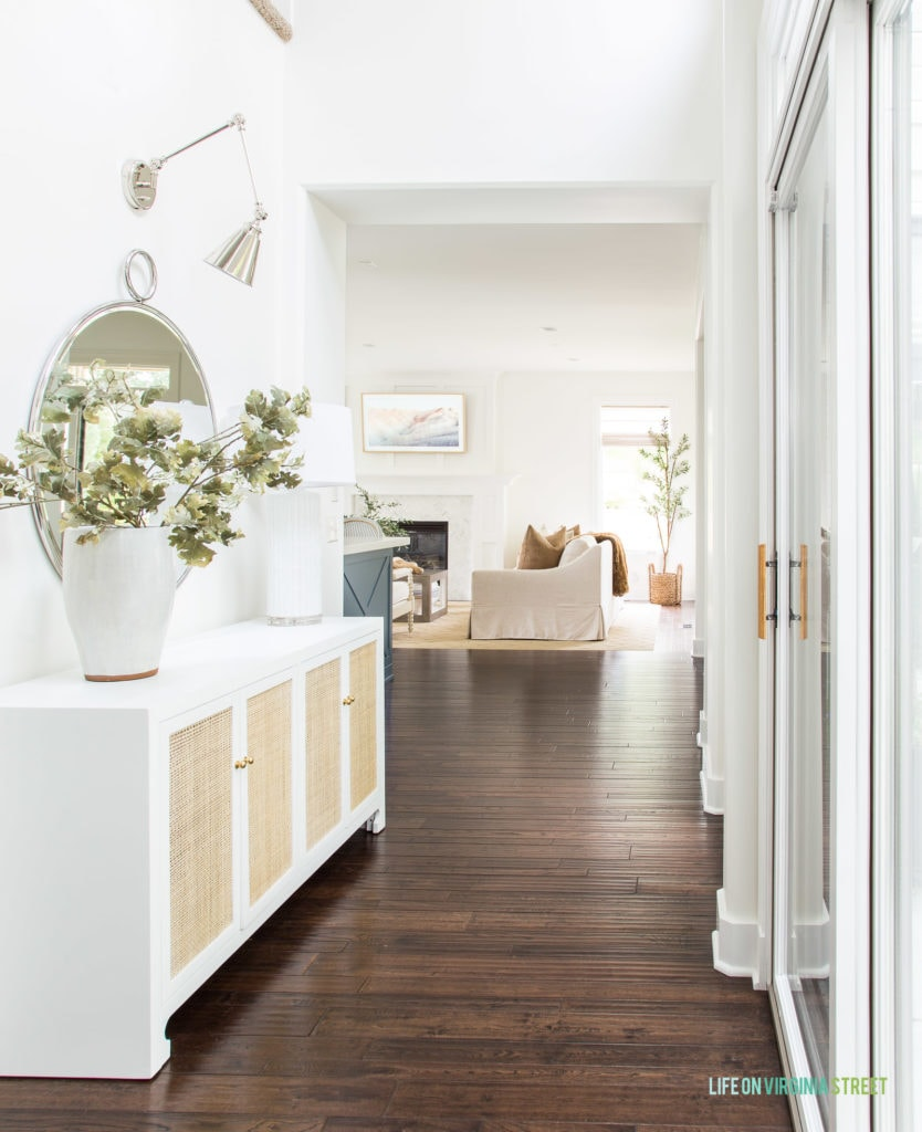 A tall white ceramic vase in an entryway with a white and cane console table and silver accents.