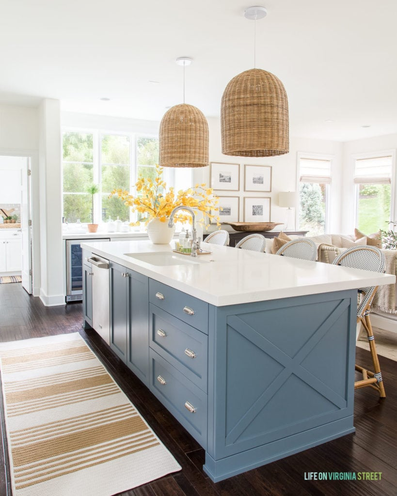 A coastal inspired kitchen with walls and cabinets painted Benjamin Moore Simply White and kitchen island painted Benjamin Moore Providence Blue.
