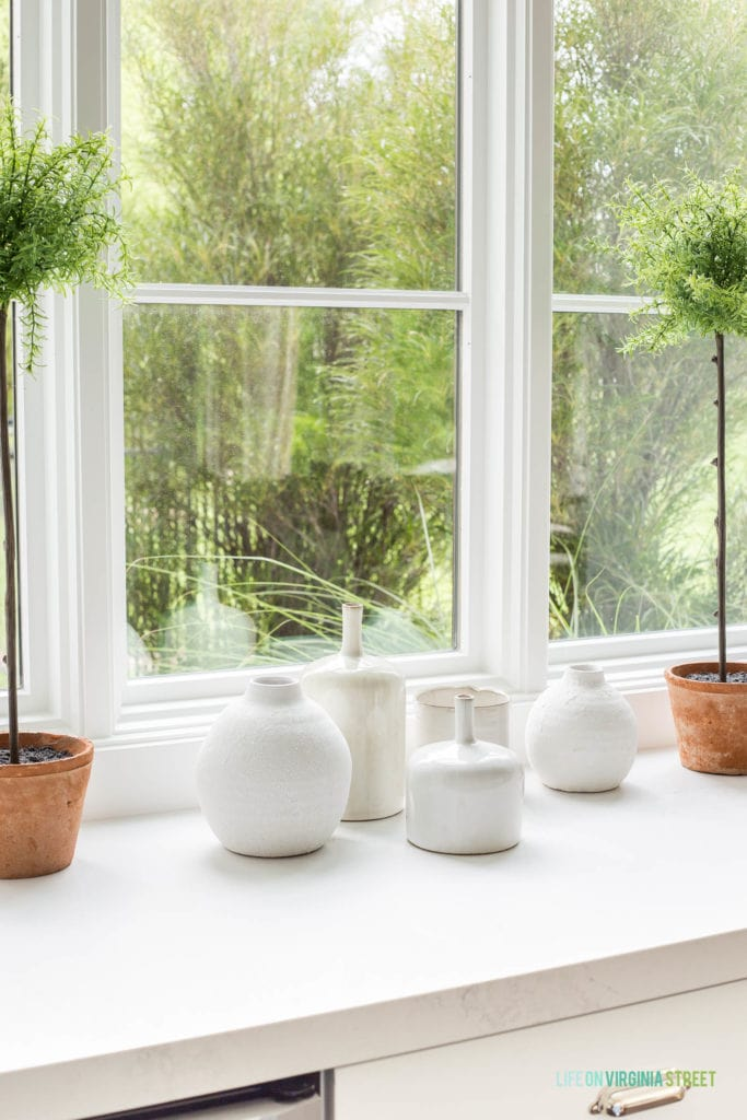 A collection of small white ceramic vases displayed as a grouping.