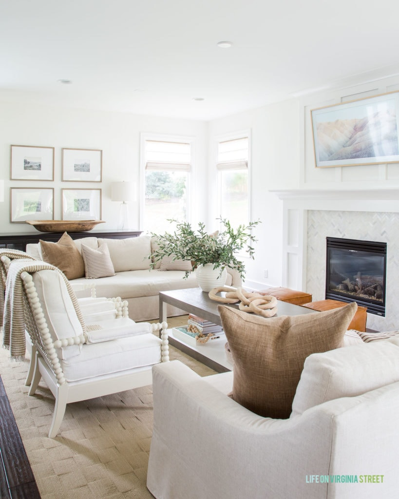 A coastal living room with neutral couches and throw blankets.   Plus a white fireplace and mantel.