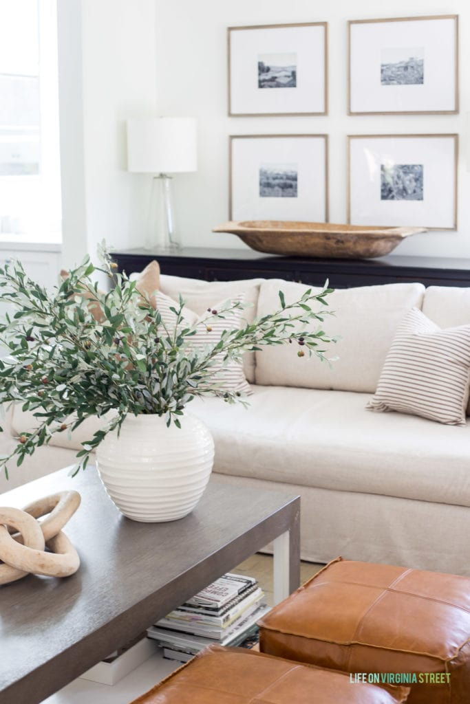 A large white ceramic vase filled with faux olive stems in a neutral living room.