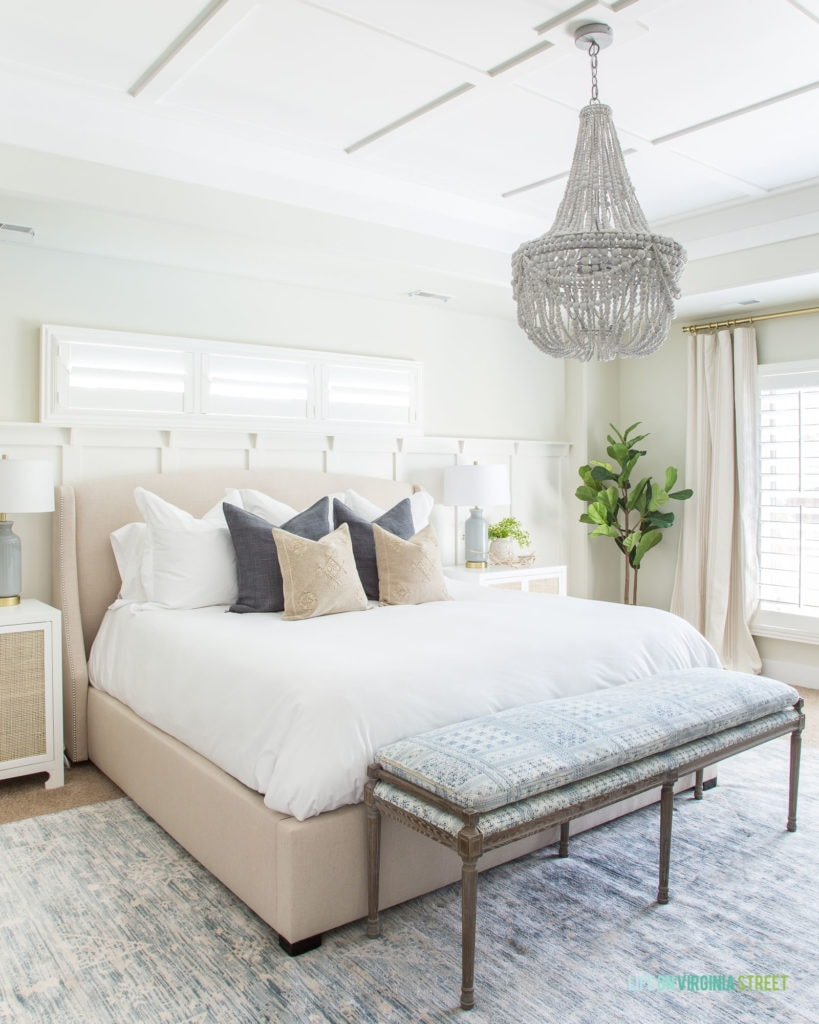 A coastal inspired master bedroom with white and cane nightstands, white wood bead chandelier, blue and white patterned bench with wood legs, white bedding, and blue and white accents.
