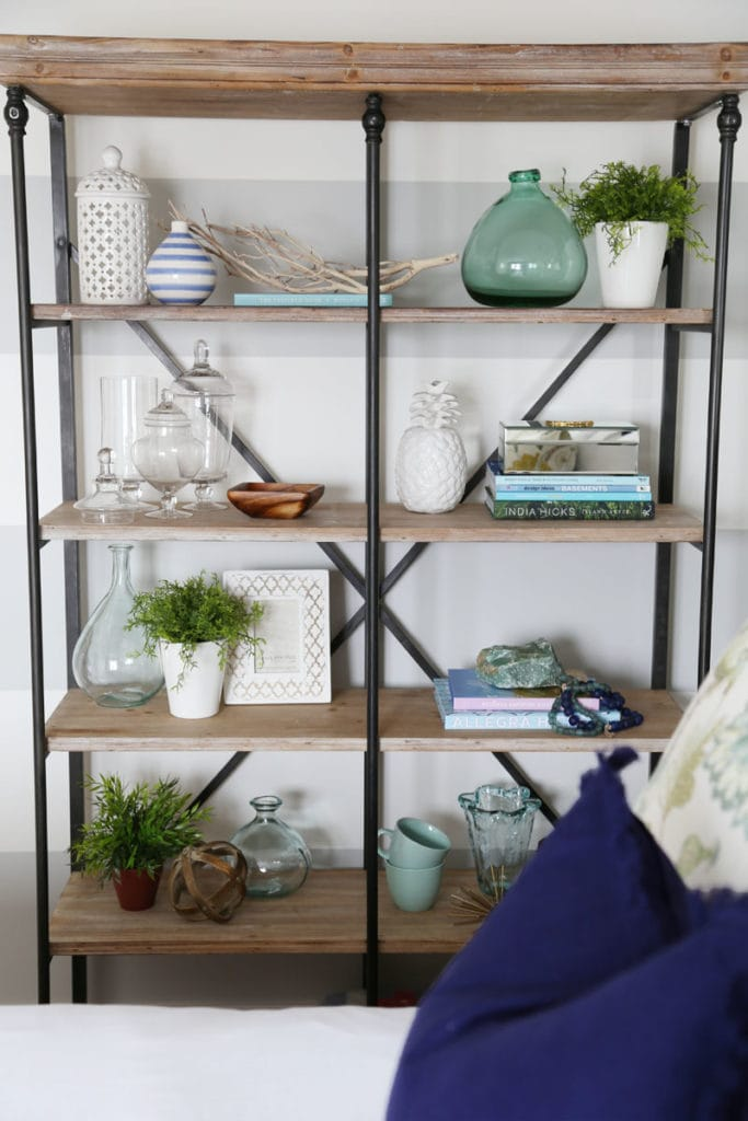 Open shelving unit with green glass, clear glass, tea cups and books.