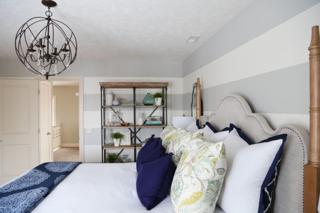 An orb chandelier above the bed in the guest bedroom, with open shelving beside the bed.