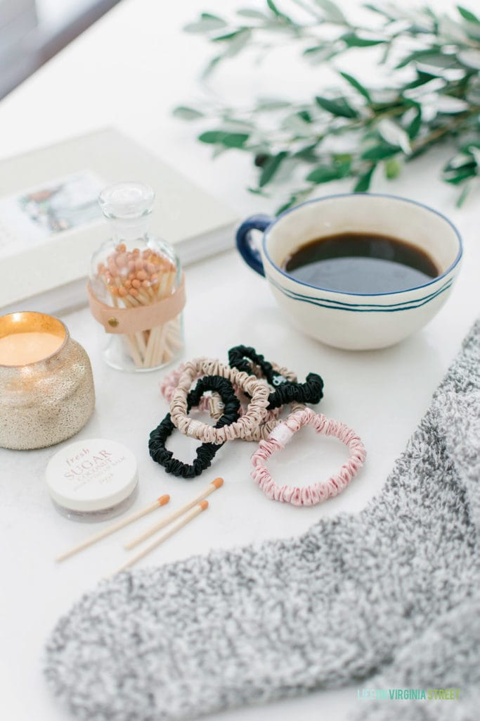 A tea cup, bracelets and a candle.
