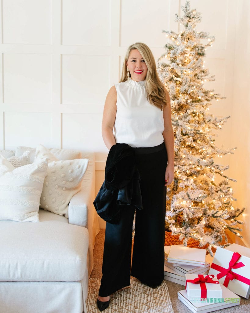 A dressy Christmas outfit from the Gibsonlook x Hi Sugarplum holiday collection. Includes a bow back sleeveless top, wide leg black pants, and a velvet blazer in a room with a linen sectional and flocked Christmas tree.
