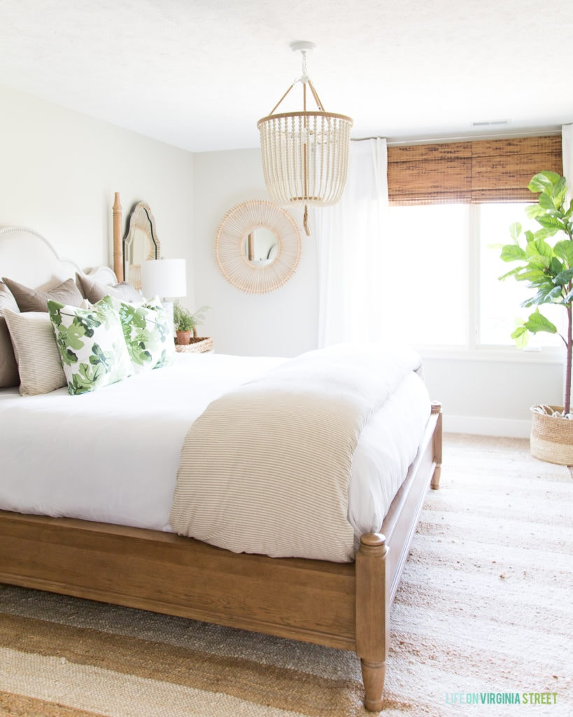 The guest bedroom with a wood bed frame, a beaded chandelier over the bed, a large plant by the window.