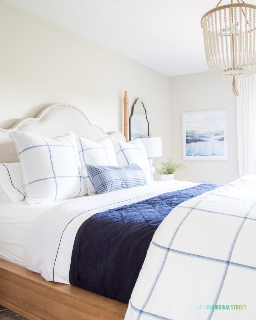 A blue sateen blanket on the bed with blue and white striped pillows.