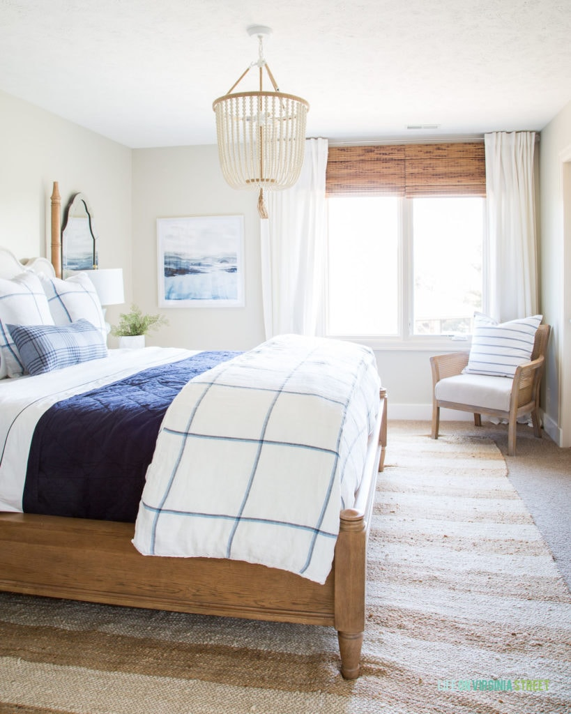 The guest room with greige walls, a wooden bed with a blue and white blanket. There is a beaded chandelier above the bed.