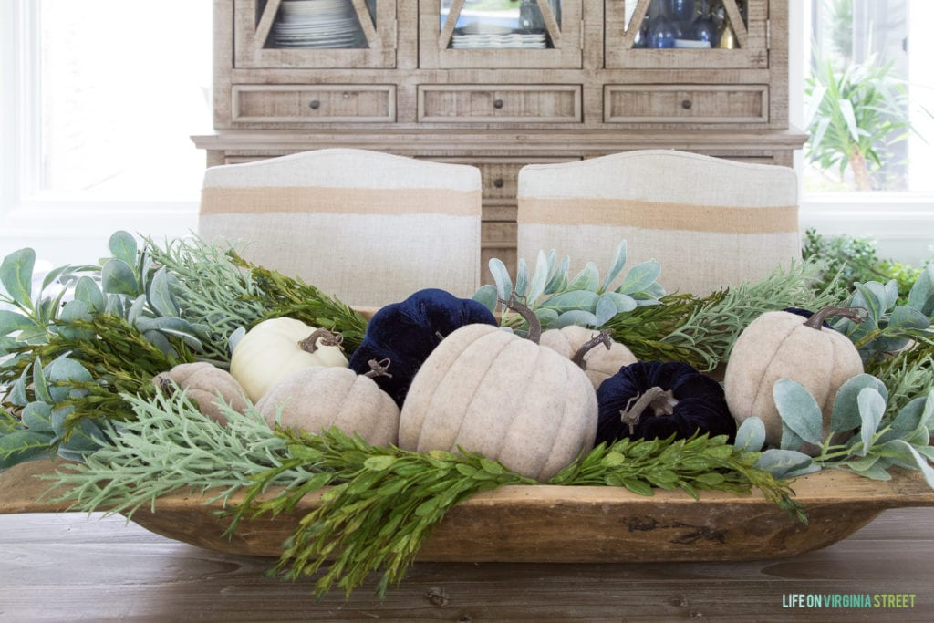 A wooden bowl filled with white and dark blue pumpkins and greenery on the dining room table.