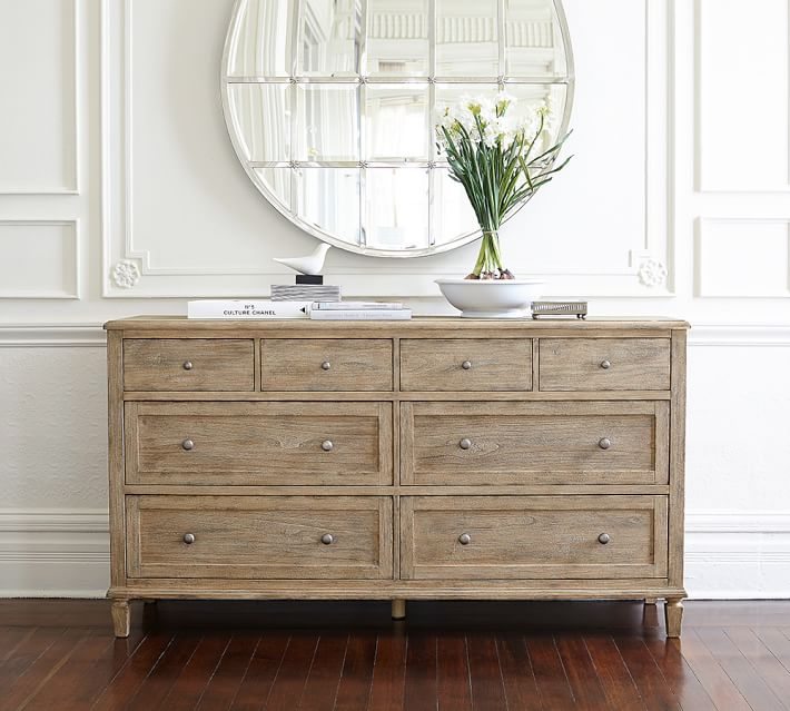 A light wood dresser with multiple drawers and a round silver mirror hung above it.
