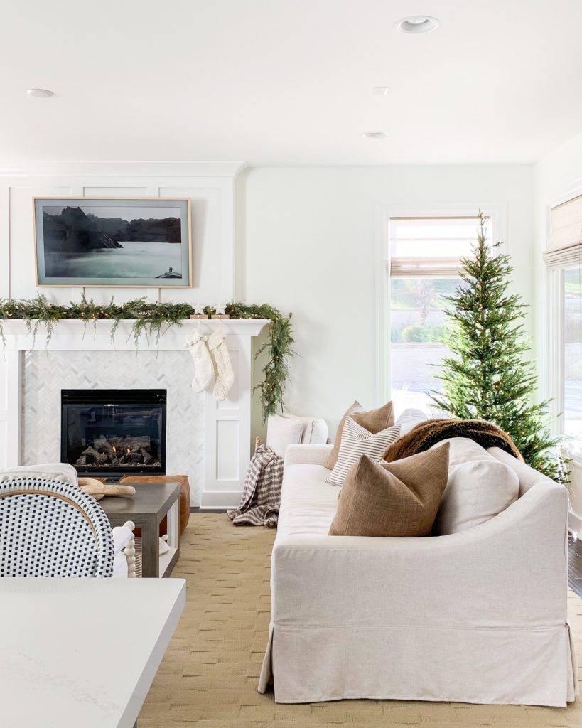 A neutral coastal living room with a Christmas tree in the corner and a mantel decorated.