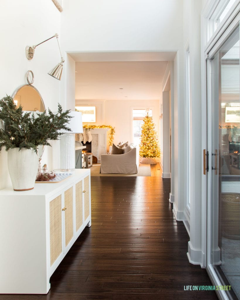 A Christmas hallway with a cane console table, nativity scene, swing arm sconces and a view of the Christmas tree.