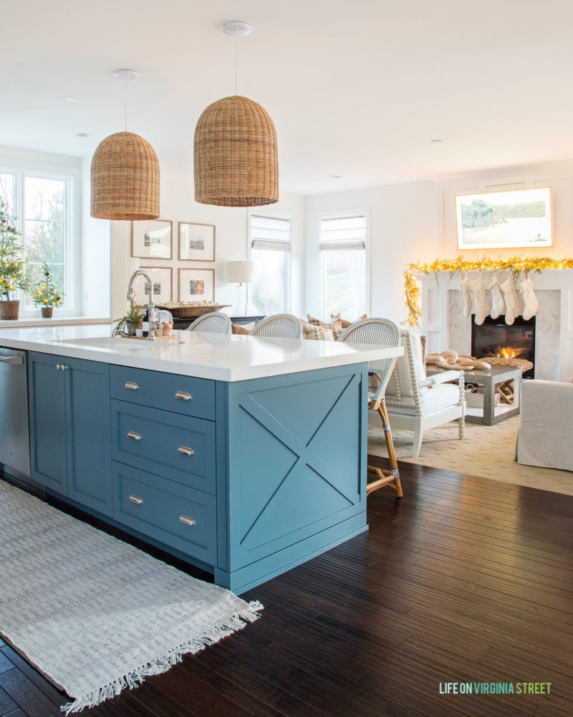 Christmas kitchen with blue island and stocking hung over the fireplace.