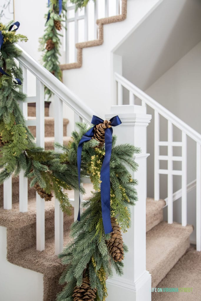 Christmas garland on a white railing tied with navy blue grosgrain ribbon.