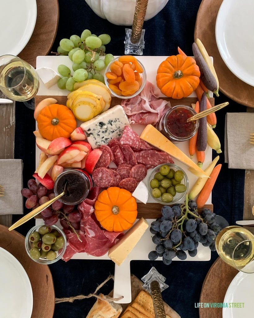 A colorful charcuterie tray that's perfect for your Thanksgiving table setting or fall! Love the addition of pumpkins and harvest veggies!
