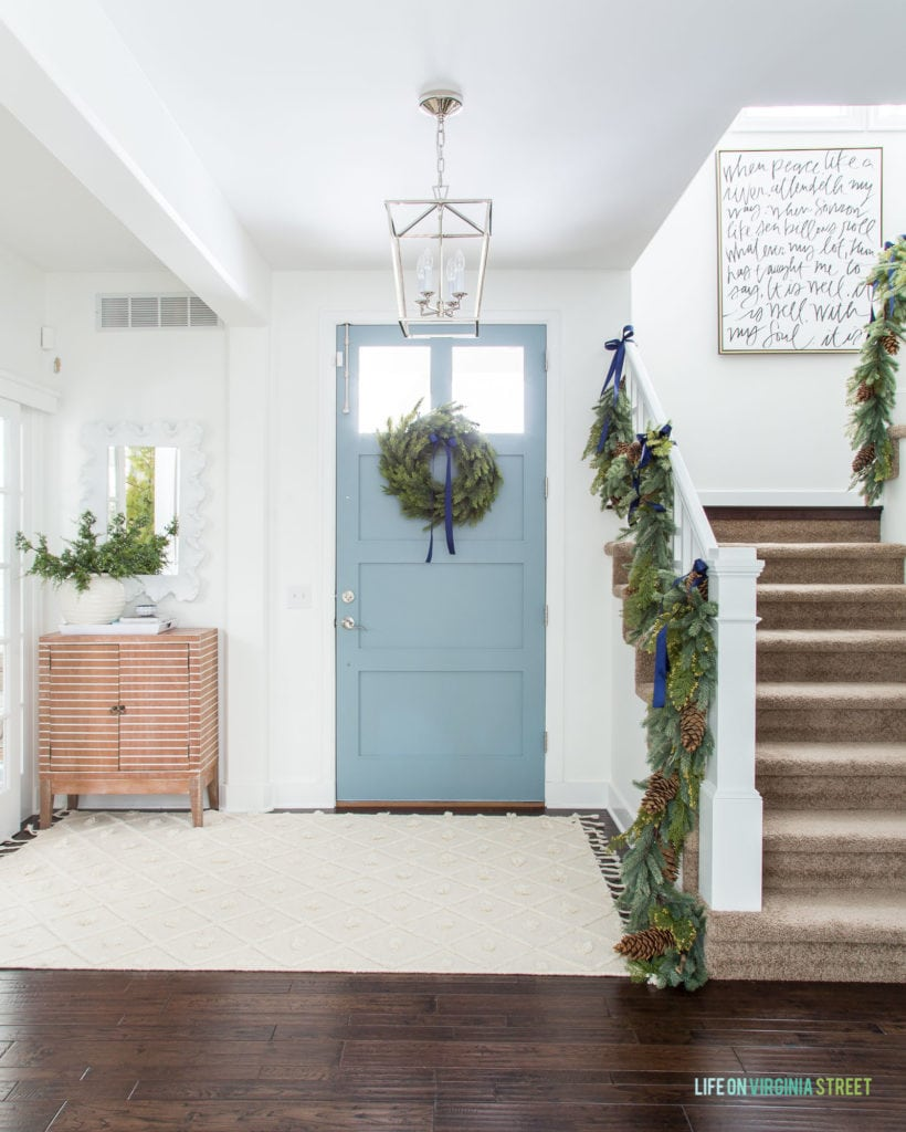 Blue Christmas decor in a coastal inspired entryway! I love the garland on the staircase and the 'It Is Well' handwritten art!