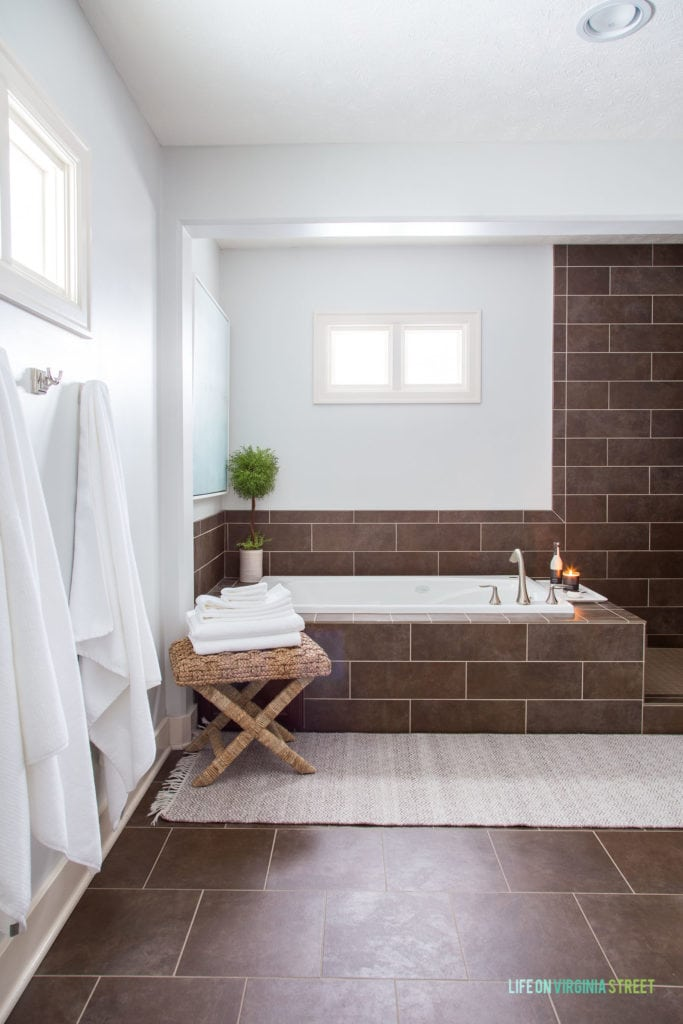 A bathtub in the corner of the bathroom with a small table with towels on it beside the tub.