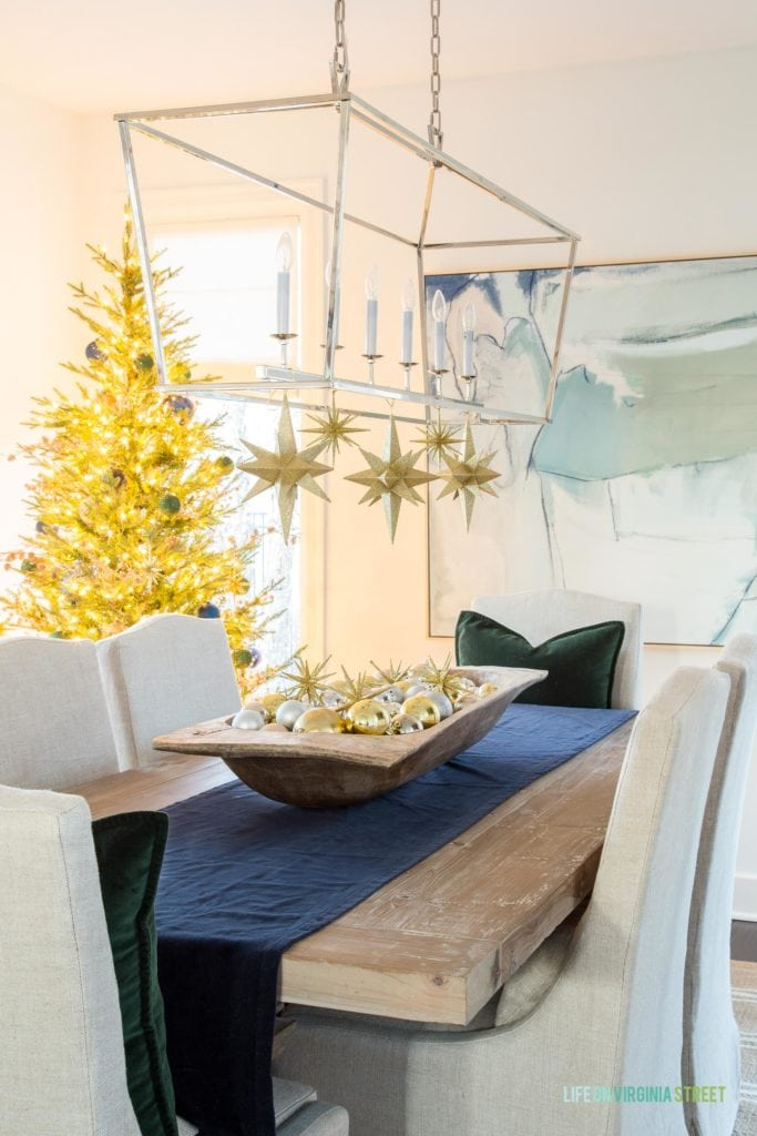 I love these large gold stars hanging from this dining room chandelier, along with the dough bowl filled with ornaments paired with the navy blue and dark green velvet!