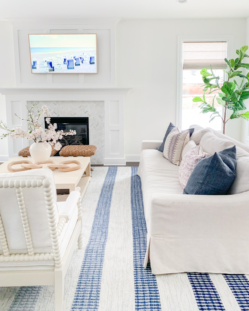 A spring living room with blue and white striped rug, linen sofa, white spindle chairs, faux cherry blossom stems and Etsy spring pillows!