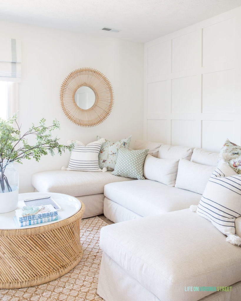DIY throw pillows with a zipper. Shown with a linen Pottery Barn sectional, striped toss pillows, a board and batten wall, rattan mirror and a bamboo coffee table.
