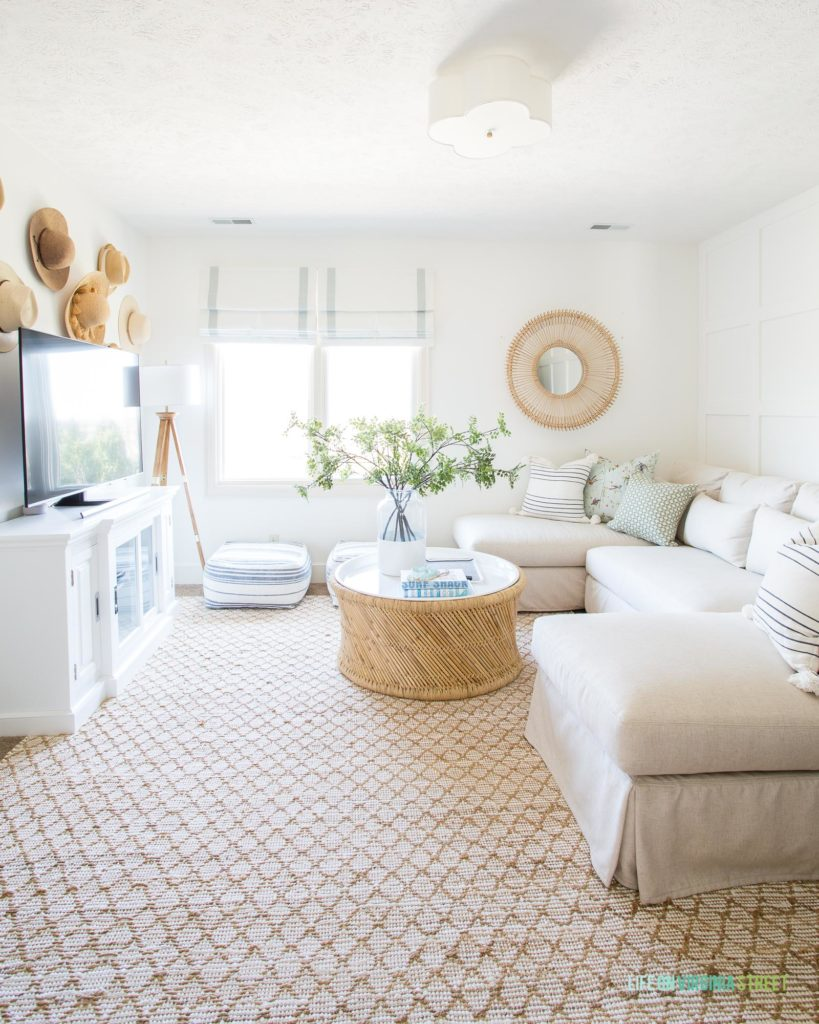 A coastal inspired den with a linen sectional, Benjamin Moore Simply White walls, and cane and rattan accents.