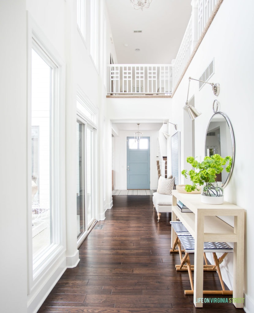 This 2020 spring home tour is filled with lots of blue and white decor along with greenery and floral stems. I love this blue front door, raffia console table, round mirror, striped benches and more!
