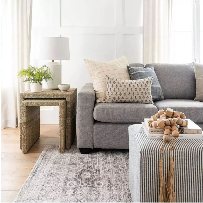 A beautiful living room designed with pieces from the Studio McGee collection at Target. I love woven nesting tables, white ceramic lamp, antique style rug, block print pillow, striped ottoman and wood beads.
