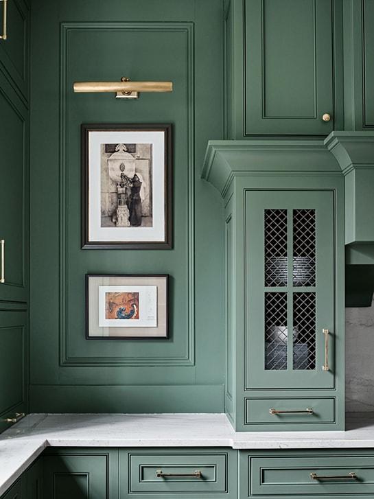 Farrow & Ball Green Smoke kitchen cabinet details with a brass light hung over artwork.