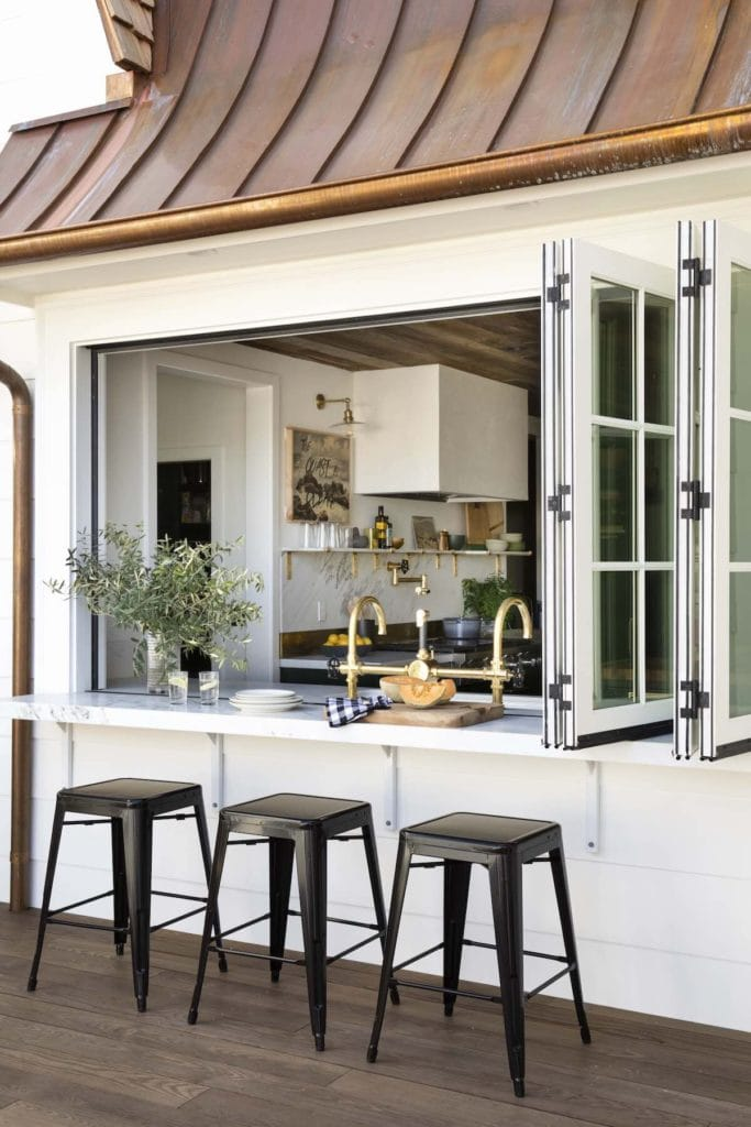 Pool house ideas including this outdoor bar area with folding glass doors on the bar top.