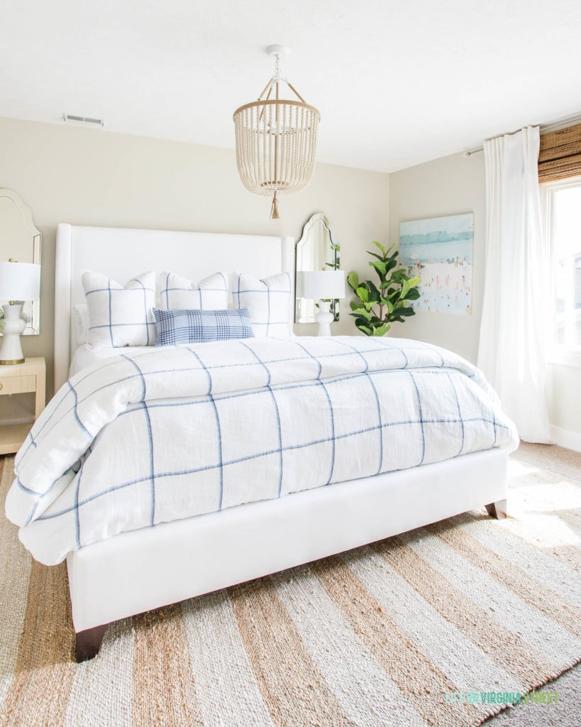 A bedroom with a white upholstered bed frame, blue and white bedding, a white bead chandelier, striped rug, and coastal art.