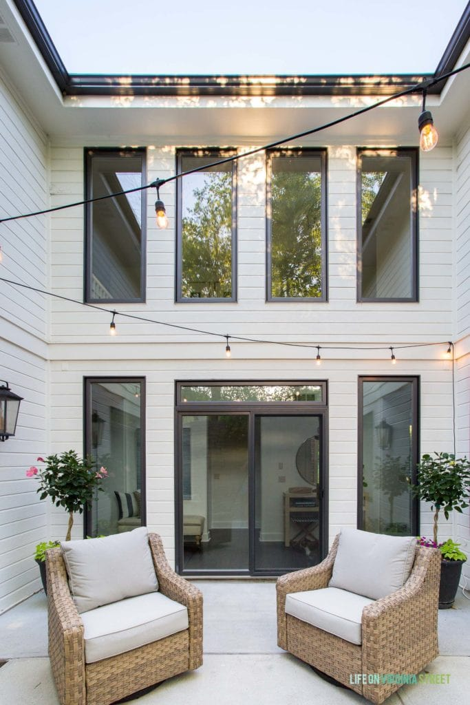 An outdoor courtyard on a white house with black window trim. Includes natural woven swivel chairs, string lights, and outdoor lanterns.