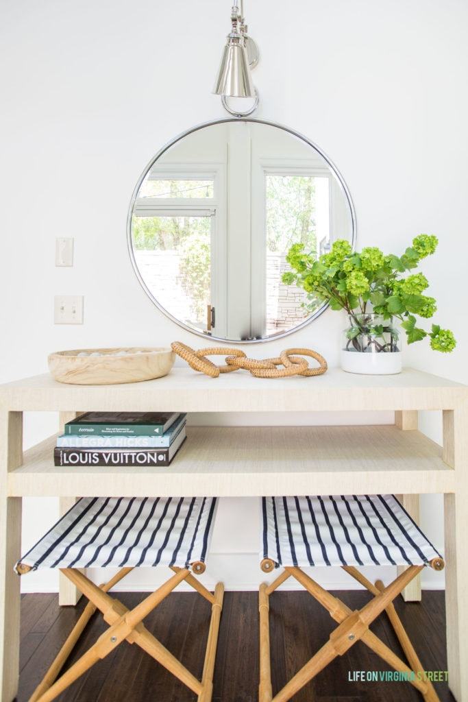 A light raffia console stable styled with a wood bowl, wicker chain, faux viburnum stems, and books. There is a round mirror over the table and striped x-benches below it.