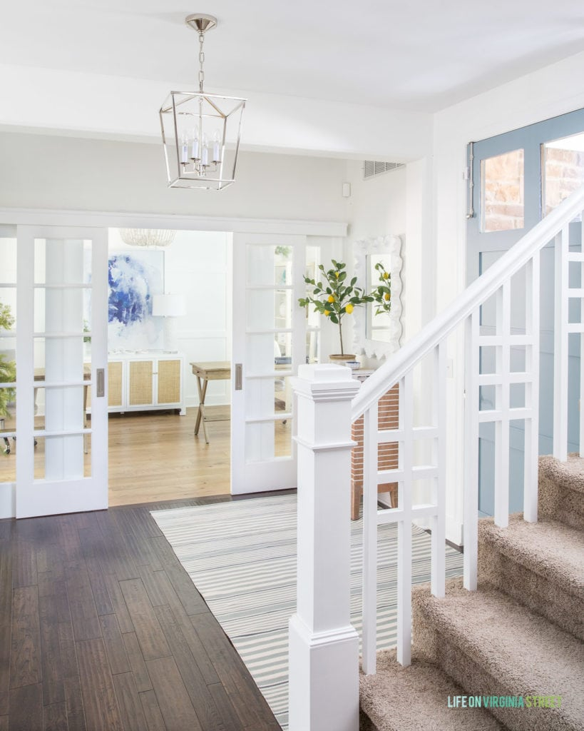 A coastal inspired entryway with a blue gray painted interior front door, a striped rug, white walls and a white board & batten grid wall in the background with a home office.