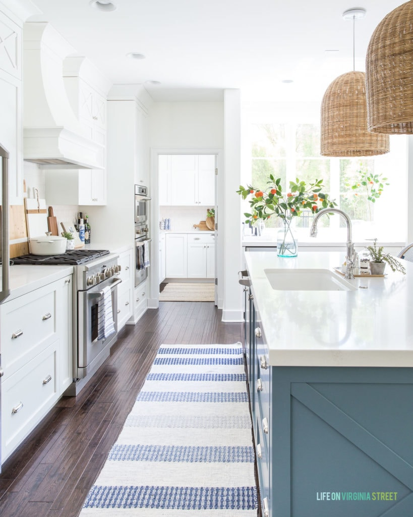 A kitchen with a blue island and white cabinets. There is a blue and white striped rug, basket pendant light fixtures over the island, and faux orange stems in a vase.