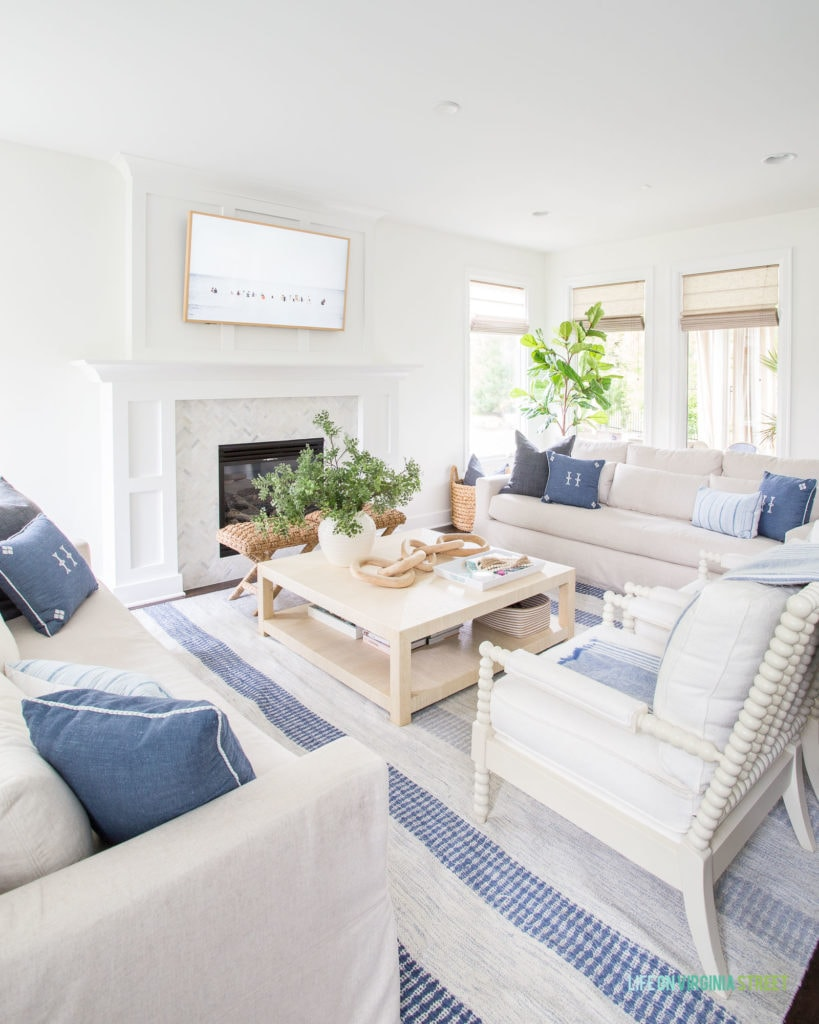 A coastal living room with blue and white striped rug, raffia coffee table, linen sofas, white spindle chairs, blue and white pillows and a Frame TV.
