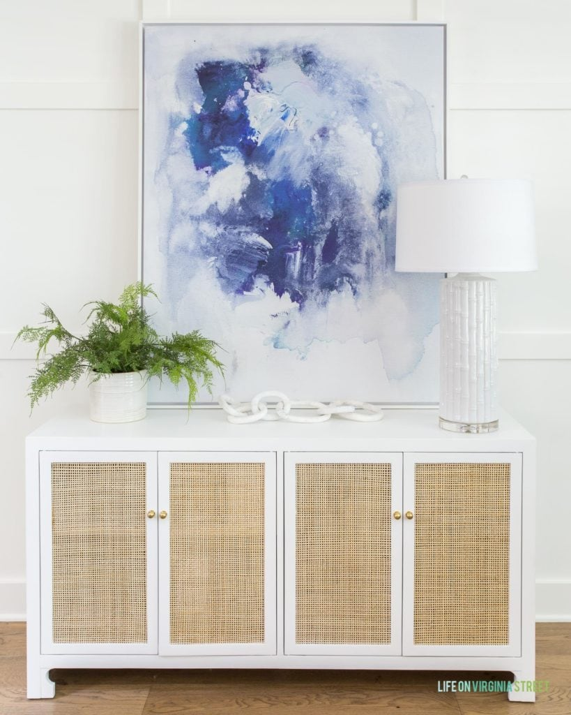 A white and natural cane console table styled with a faux fern, blue abstract art, a marble chain, and a white ceramic bamboo lamp.