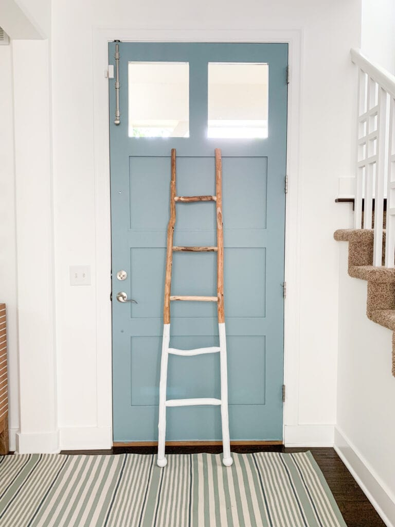 A coastal style entryway with Simply White Walls, Water's Edge painted door, striped rug, and a paint dipped wood ladder.